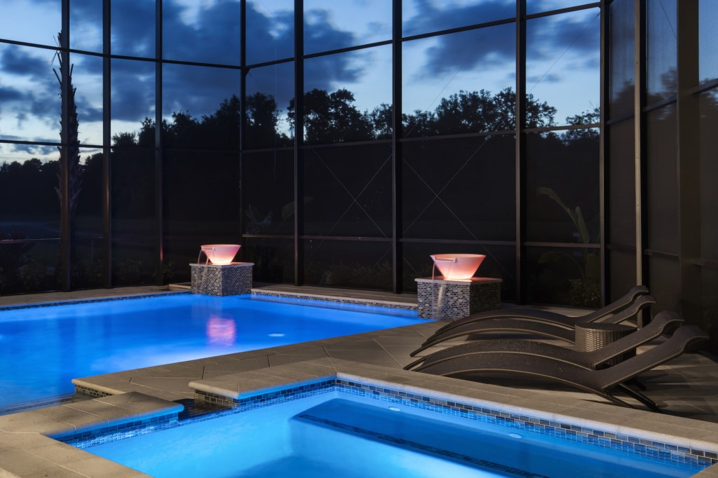 Lighted Water Features of Pool at Twilight - Hopesail - 10 Bedroom Reunion Resort Vacation Home - Homes4uu