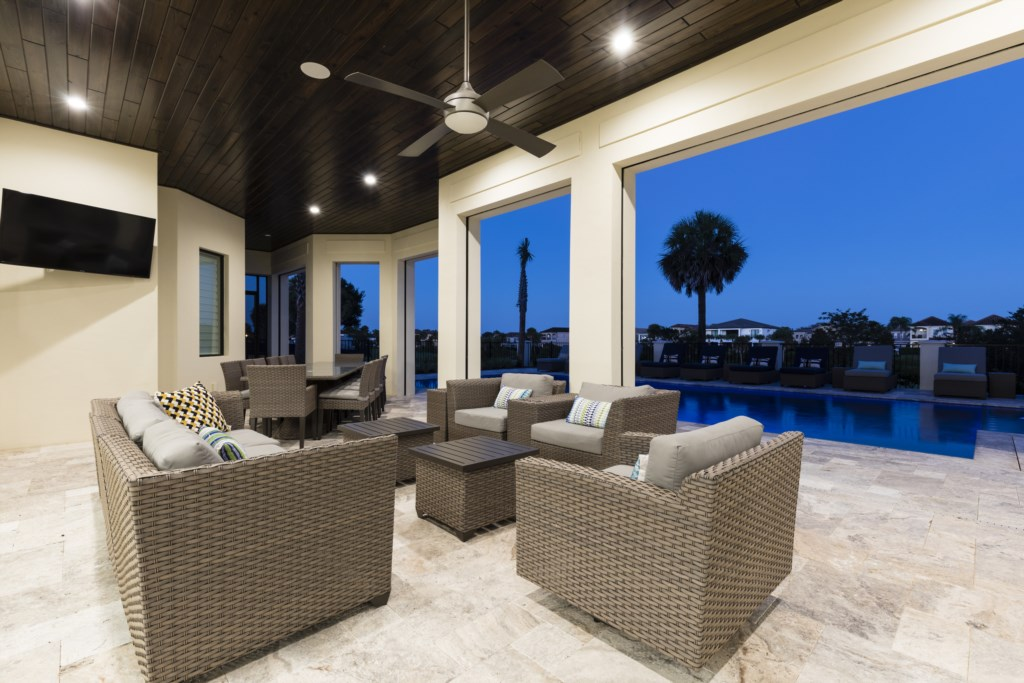 Lanai at Twilight With Huge TV - Captain's Chair - 9 Bedroom - Luxury Orlando Vacation Home - Homes4uu