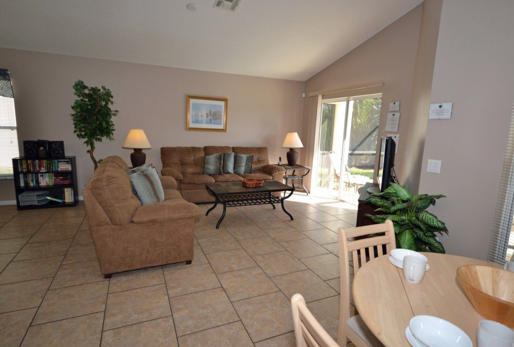 Living Room with Doors to the Pool and Lania - Palm Villa - 4 Bedroom - Orlando Golf Course Vacation Home - Homes4uu